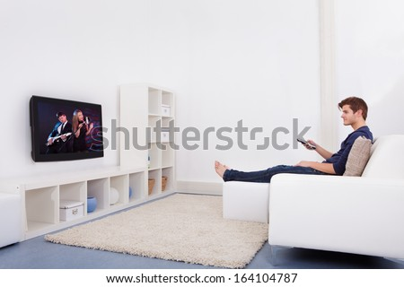 Young Man Sitting On Couch Watching Television - stock photo