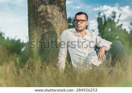 Young man sitting on grass against a tree. Handsome guy repose in nature. Outdoors - outside - stock photo