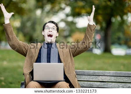 Young Man Sitting On Park Bench, Celebrating On His Laptop - stock photo