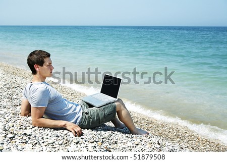Young man sitting on pebbled beach with laptop - stock photo