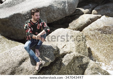 Young man sitting on rocks, looking away  - stock photo