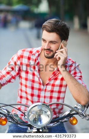 Young man sitting on scooter and talking on the mobile phone. Vertical close up portrait of a handsome bearded male with a smartphone - stock photo