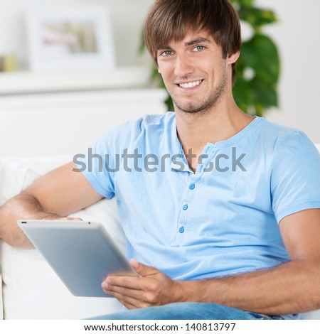 young man sitting on sofa an working with tablet - stock photo