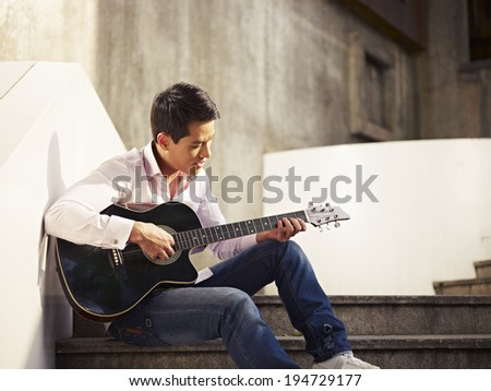 young man sitting on steps playing guitar and singing. - stock photo