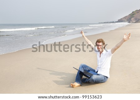 Young man sitting on the beach with laptop arms stretched - stock photo