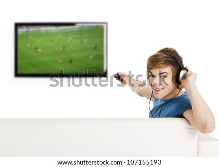Young man sitting on the couch using a remote control and watching a football game on tv - stock photo