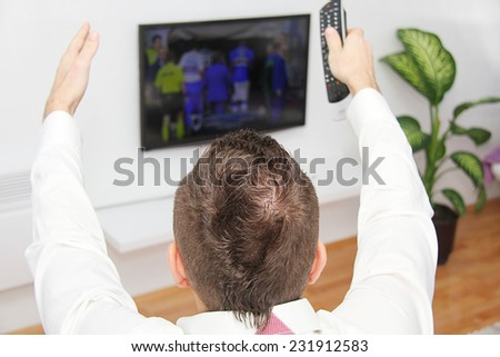 Young man sitting on the couch watching a football game on tv - stock photo