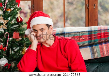Young man sitting on the couch with santa hat in deep thoughts at home, looking sad at camera, over christmas tree background on living room. - stock photo