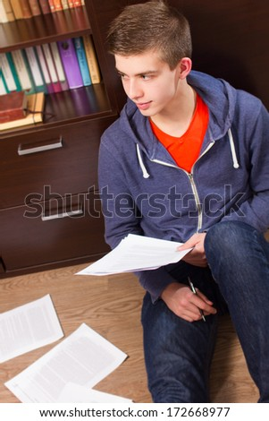 young man sitting on the floor and learning - stock photo