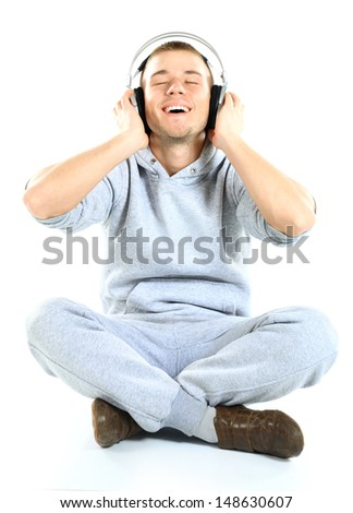 young man sitting on the floor listening to music - stock photo