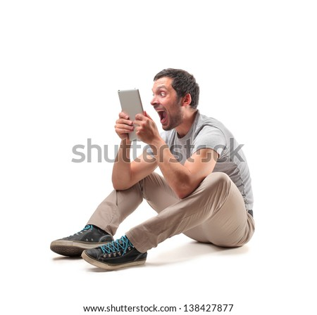 young man sitting on the floor looks with stupor the tablet - stock photo