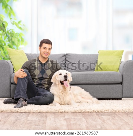 Young man sitting on the floor with his dog at home shot with tilt and shot lens - stock photo