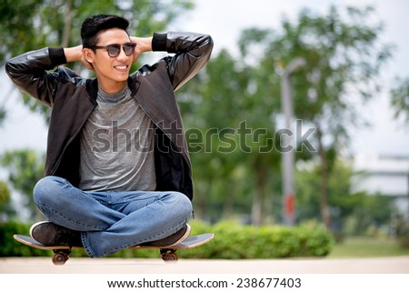 Young man sitting on the skateboard with hands behind his head - stock photo