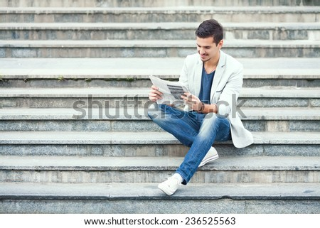 Young man sitting on the stairs reading newspaper - stock photo