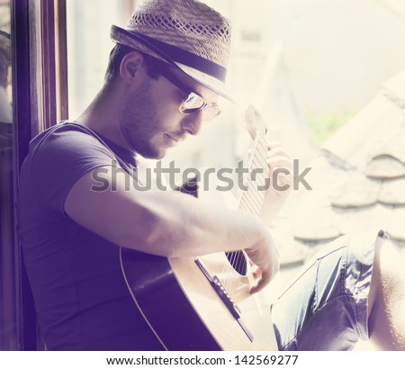 Young man sitting on the window playing the guitar - stock photo