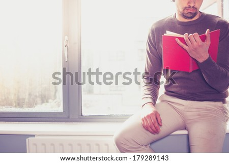 Young man sitting on window sill and reading a red book - stock photo