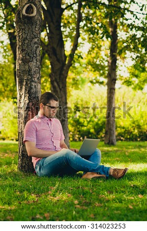 Young man sitting with Laptop Computer in the park - stock photo