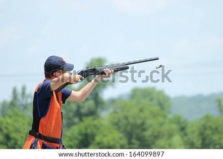Young man skeet shooting with airborne shell - stock photo