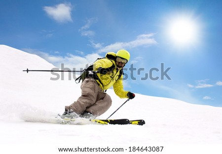young  man skiing on mountain slopes at winter season and sunny day - stock photo