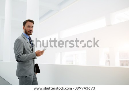 Young man skilled office worker is holding mobile phone and looking at camera, while is standing in hallway company near copy space. Serious male manager is searching information on cell telephone - stock photo
