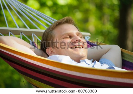 Young man sleeping in a hammock - stock photo