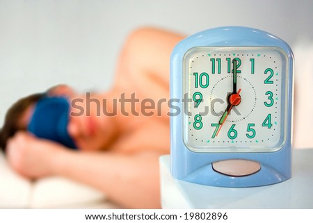 young man sleeping in his bedroom and alarm clock - stock photo