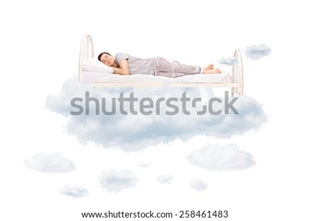 Young man sleeping on a comfortable bed in clouds isolated on white background - stock photo