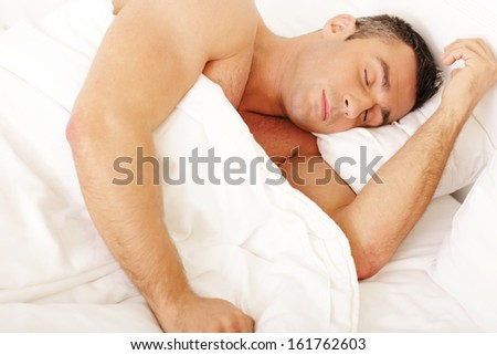 Young man sleeping on the bed at home - stock photo