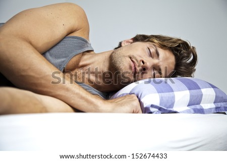 Young man sleeping peacefully in his own bed - stock photo