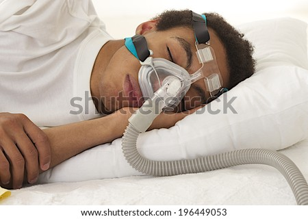 young man  sleeping with apnea and CPAP machine  - stock photo