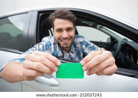 Young man smiling and holding card in his car - stock photo