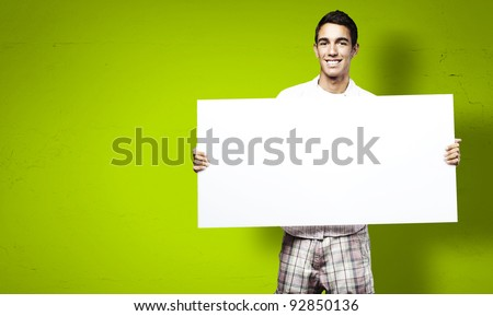young man smiling and showing a big banner against a green background - stock photo