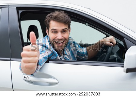 Young man smiling and showing thumbs up in his car - stock photo