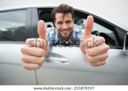 Young man smiling at camera showing thumbs up in his car - stock photo
