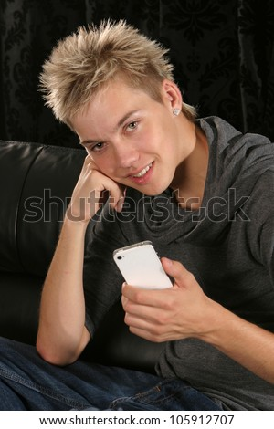 Young man smiling leaning on his elbow holding a mobile device - stock photo