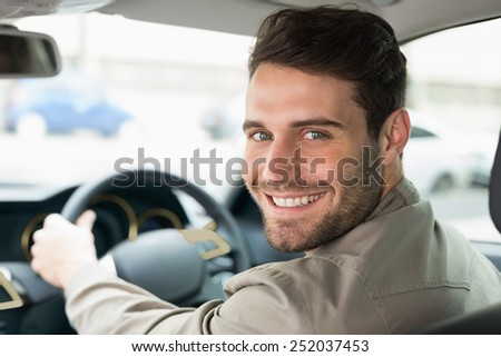 Young man smiling while driving in his car - stock photo