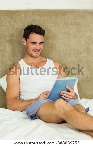 Young man smiling while using digital tablet in bedroom - stock photo