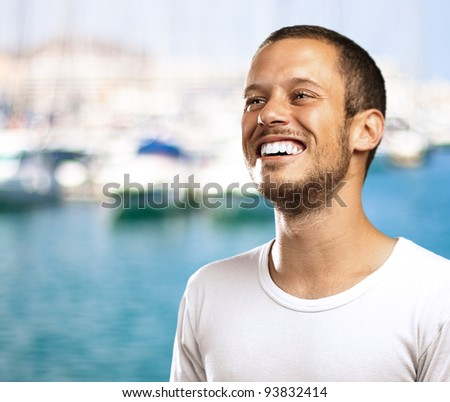 young man smiling with a harbor as a background - stock photo