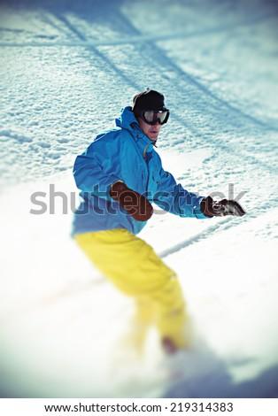 Young man snowboarding. Tilt shift effect. - stock photo