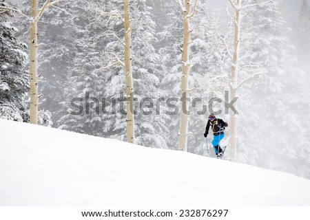 Young Man Snowshoeing Up Hill in Wintry Storm - stock photo