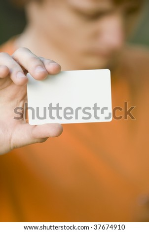 Young man somewhat in bad mood shows his blank card - stock photo