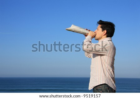 Young man speaking with a newspaper megaphone - stock photo