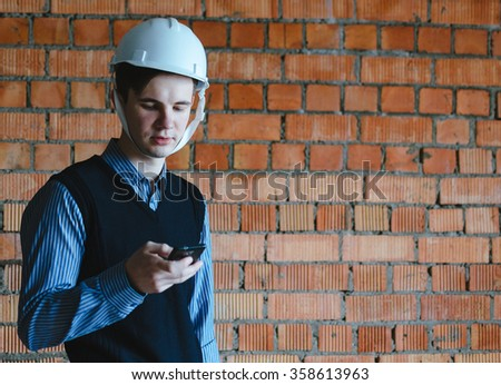 Young man specialist with phone on the orange bricks background - stock photo