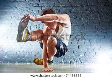 Young man sports exercises. On wall background. - stock photo