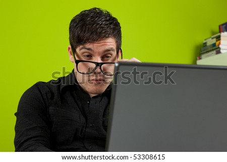 Young man squinting at the laptop - stock photo
