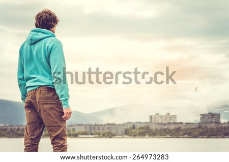 Young Man standing alone outdoor Travel Lifestyle concept with lake and city on background - stock photo