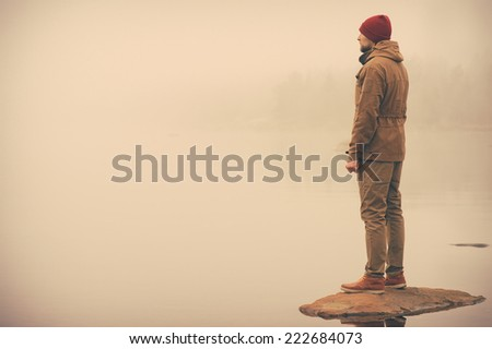 Young Man standing alone outdoor with foggy scandinavian nature on background Travel Lifestyle and melancholy emotions concept film effects colors - stock photo