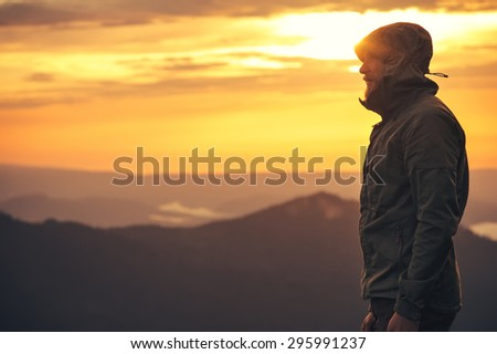 Young Man standing alone outdoor with sunset mountains on background Travel Lifestyle and survival concept  - stock photo