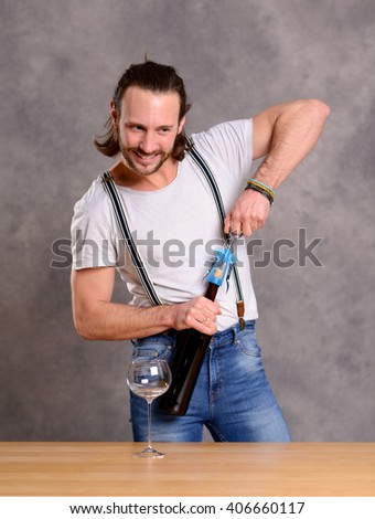 young man standing at the table and opening red wine - stock photo