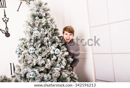 young man standing behind a Christmas tree - stock photo